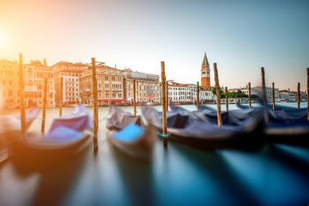 Cityscape van Venetië mening over Groot kanaal met kleurrijke gebouwen, gondels en campanille van San Marco bij de zonsondergang. Lange blootstelling beeldtechniek met beweging wazig boten en glanzend water Stockfoto