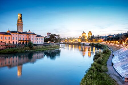 evening church: View on Adige river with Verona cathedral and saint George church at the evening in Verona city in Italy Stock Photo