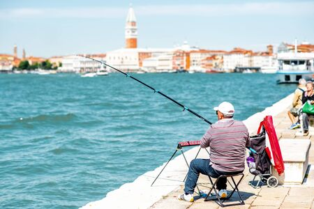 campanille: Venice, Italy - May 18, 2016: Elder man fishing on the coast in front of San Marco tower in Venice