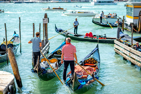 gondoliers: Venice, Italy - May 18, 2016: Gondoliers sail on gondolas full of tourists in water canal in Venice. Gondola is a traditional venetian boat and famous tourist attraction.