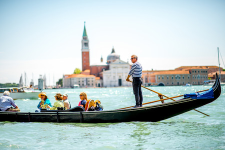 gondoliers: Venice, Italy - May 18, 2016: Gondoliers sail on gondolas full of tourists with San Georgio Maggiore island on the background in Venice.