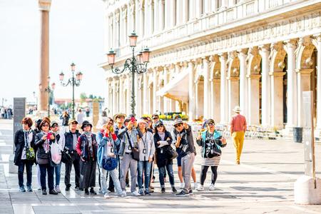 베니스, 이탈리아 - 2016년 5월 18일는 : 아시아 관광객의 그룹은 산 마르코 광장에 서있다. 베니스는 아시아 사람들 사이에서 매우 인기있는 관광지입니