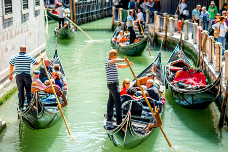 gondoliers: Venice, Italy - May 18, 2016: Gondoliers sail on gondolas full of tourists in the narrow water canal in Venice. Gondola is a traditional venetian boat and a famous tourist attraction. Editorial
