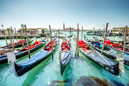 gondoliers: Venice, Italy - May 18, 2016: Gondoliers waiting for clients near San Marco square. Sailing in godolas is most popular tourist attraction in Venice