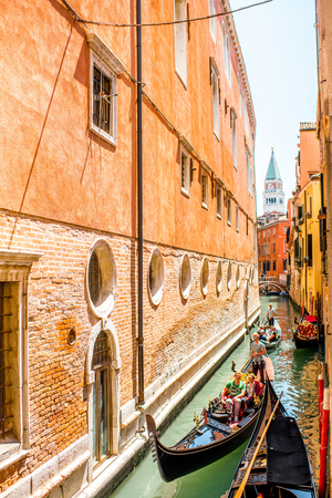gondoliers: Venice, Italy - May 18, 2016: Gondoliers sail on gondolas full of tourists in the narrow water canal in Venice. Gondola is a traditional venetian boat and famous tourist attraction.