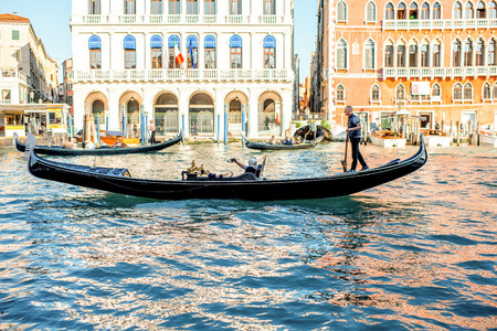 Venice, Italy - May 18, 2016: Gondolier sail with tourists in gondola in Grand canal in Venice. Gondola is a traditional venetian boat and a famous tourist attraction. Editorial