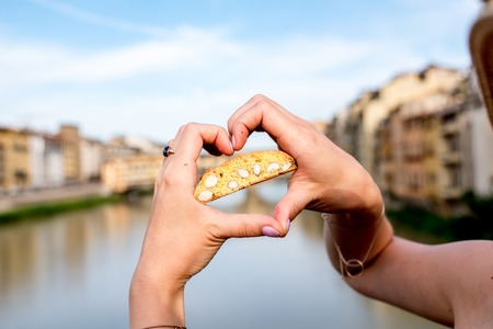 Female hands holding cantuccini cookie on the river background in Florence city in Italy. Cantuccini is traditional italian almond biscuits Stock Photo