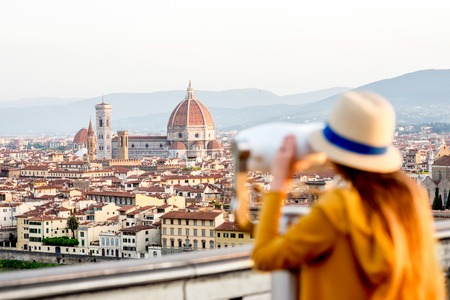 Young female tourist looking with telescope on the old town of Florence from Michelangelo square in the morning in Italy. Focus on the background Stock Photo