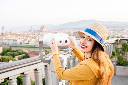michelangelo: Young female tourist looking with telescope on the old town of Florence from Michelangelo square in the morning in Italy Stock Photo