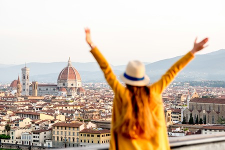 Young female tourist with raised hands looking on the old town of Florence from Michelangelo square in the morning in Italy. Back focus