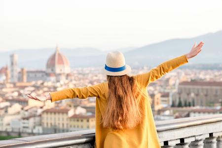 若い女性観光客がイタリアの朝のミケランジェロ広場からフィレンツェの古い町の眺め。
