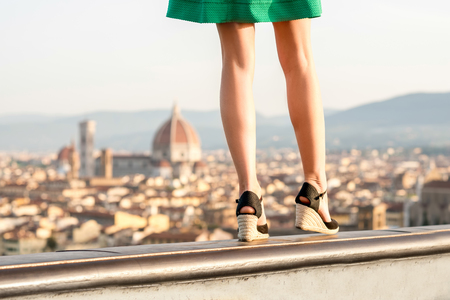 heals: Beautiful womans legs on the heals on the old town background in Florence.