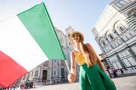 promoting: Young smiling female traveler standing with italian flag in front of the famous Santa Maria del Fiore cathedral in Florence. Promoting tourism in Italy Stock Photo