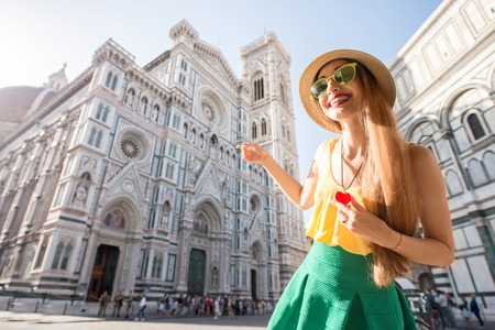 promoting: Young female traveler dressed colorful with heart pendant showing famous Santa Maria del Fiore cathedral in Florence. Promoting tourism in Italy Stock Photo