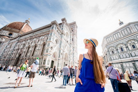 crowded space: Young female traveler standing on Cathedral square in front of Santa Maria del Fiore church in Florence. Having great vacations in Italy