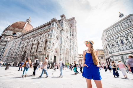 Young female traveler standing on Cathedral square in front of Santa Maria del Fiore church in Florence. Having great vacations in Italy