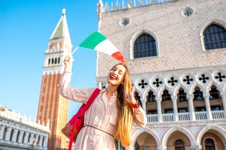 Young female traveler waving italian flag on San Marco square in Venice. Happy vacations in Venice Stock Photo