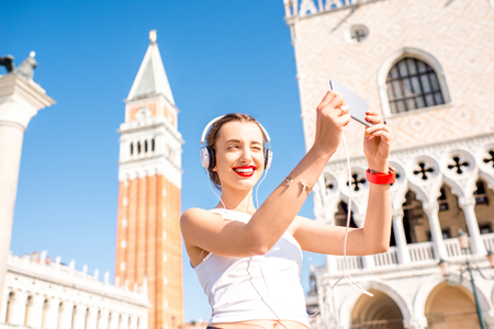 saint marks: Young woman in sportswear taking selfie photo in front of Saint Marks tower in the center of Venice. Morning exercise in the old town of Venice