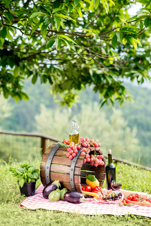 Lots of tasty italian food on the napkin and wooden barrel outdoors in the countryside with tree on the background Stock Photo