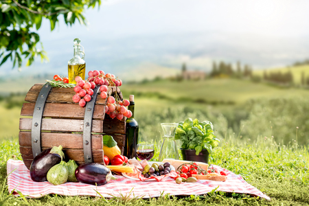 italian landscape: Lots of tasty italian food on the napkin and wooden barrel outdoors on the tuscany landscape background Stock Photo