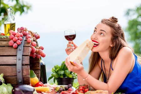 Beautiful woman tasting parmesan cheese lying on the grass with lots of tasty italian food and wine in the countryside in Tuscany. Stock Photo