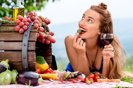Beautiful woman tasting olive lying on the grass with lots of tasty italian food and wine in the countryside in Tuscany. Standard-Bild