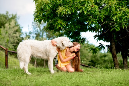 Young and happy woman playing with Maremma italian sheepdog on the lawn in the countryside in Tuscany