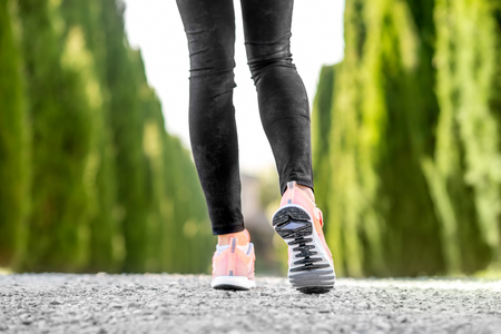 Female legs in sport sneakers in start position on the gravel road