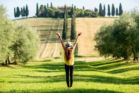 back alley: Young woman in hat and yellow shirt enjoying beautiful Tuscan landscape in Italy.