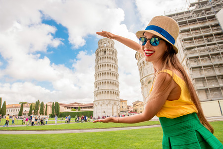 Young female traveler having fun in front of the famous leaning tower in Pisa old town in Italy. Happy vacations in Italy Imagens - 61967991