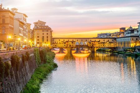 Illuminated cityscape view on Arno river with famous Ponte Vecchio bridge and buildings on the riverside on the sunset in Florence