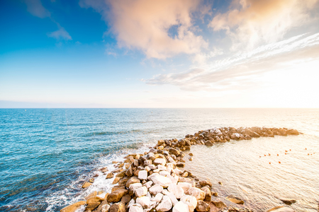 to spit: Beautiful seascape with stony spit on the sunset Stock Photo