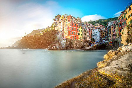 Landscape view on the old coastal town Riomaggiore in the small valley in the Liguria region of Italy. Long exposure image technic with glossy water Stockfoto