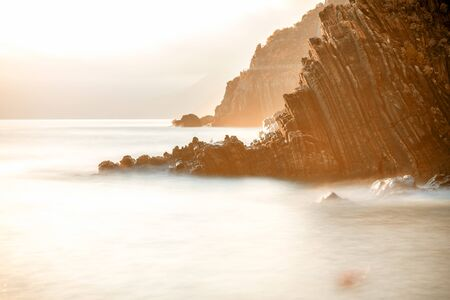 Rocky coastline on the sunset. Long exposure image technic Stockfoto