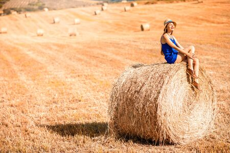 blue dress: Young woman in blue dress enjoying nature on the hayfield in Tuscany in Italy Stock Photo