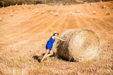 blue dress: Young woman in blue dress pushing hay roll on the hayfield in Tuscany in Italy