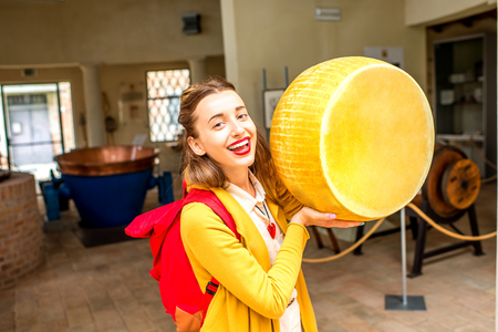 Young woman holding a big head of Parmesan cheese at the old manufacturing in Italy