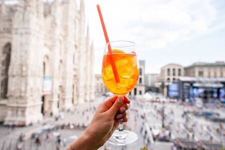 spritz: Holding a glass of spritz aperol drink on the main square with Duomo cathedral on the background in Milan city Stock Photo