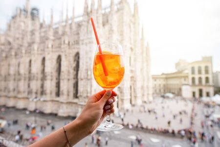Holding a glass of spritz aperol drink on the main square with Duomo cathedral on the background in Milan city Stock Photo