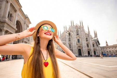 Young and happy tourist in front of the famous Duomo cathedral in Milan. Happy vacations in Milan