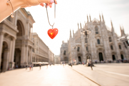 Red pendant in form of the heart on the central square background with Duomo cathedral in Milan. Stock Photo