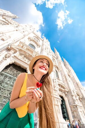 Young and happy female tourist dressed colorful in front of the famous Duomo cathedral in Milan. Having great vacations in Milan