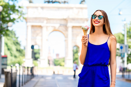 Young woman in the blue dress eating ice cream in front of the triumphal arch in Milan. Street food in Milan