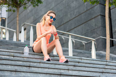 Young sports woman sitting on the stairs, resting after the morning jogging in the modern city. Healthy lifestyle in the big city.