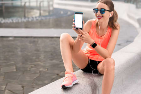 copy paste: Young sports woman showing phone with white screen to copy paste sitting on the modern bench in the city Stock Photo