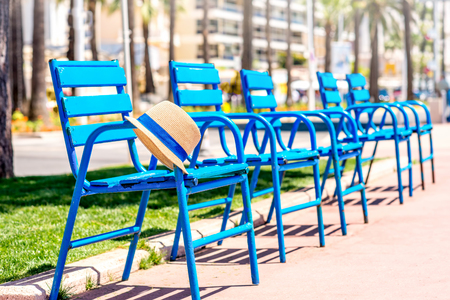 The blue chairs of the promenade with hat in Cannes city. This chairs are iconic symbol and tourist attraction of Cannes in France Imagens