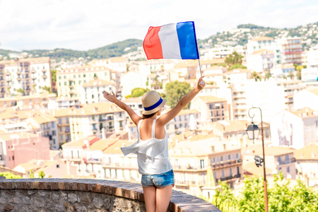 Young female traveler with flag enjoying great view on french riviera in Cannes city