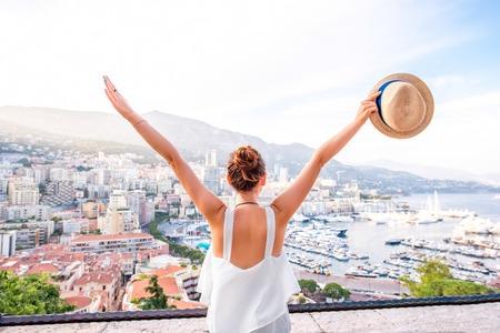 모나코의 몬테카를로 항구와 도시에서 좋은 전망을 즐기는 젊은 여성 여행자 스톡 콘텐츠