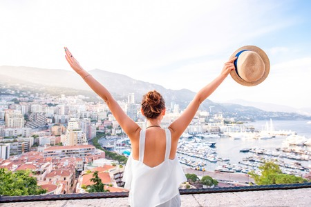 Young female traveler enjoying great view on the city with harbor in Monte Carlo in Monaco