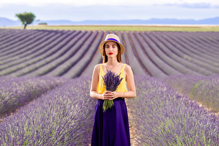 lavande: Young pretty woman in the long violet skirt standing with lavender bouquet on the lavender field in Provence in France